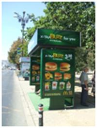 """Fig. 1. Așteptând autobuzul RATB într-o """"cutie publicitară"""" (București, Bdul Unirii, iulie 2013, foto. S. C.)"""